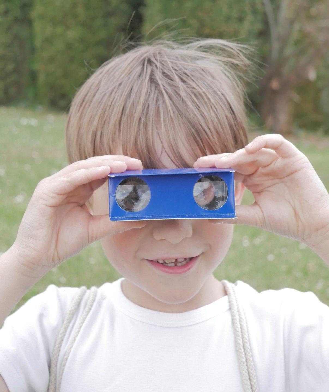 Enfant utilisant les jumelles du kit du reporter